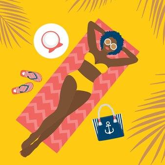 Девушка в желтом купальнике загорает на пляже. летняя сумка, шлепки, шапка.