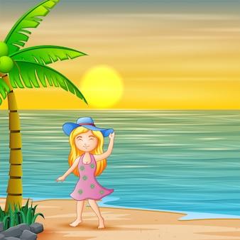 Девушка в синей шляпе, стоя на пляже на закате