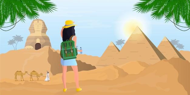 バックパックを背負った少女がエジプトのスフィンクスとピラミッドを見る