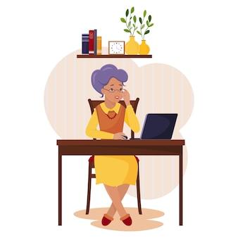 白髪の年配の女性がノートパソコンの画面で何かを注意深く読んでいます