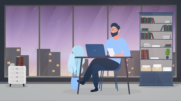 眼鏡をかけた男が彼のオフィスのテーブルに座っています。男はラップトップで働いています。オフィス、本棚、ビジネスマン、フロアランプ。オフィスワークのコンセプト。 。