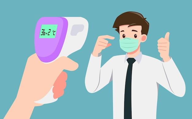 마스크를 쓴 사업가가 대중들에게 안전하다는 것을 증명하기 위해 체온을 확인하는 디지털 적외선 온도계를 들고있는 손. 코로나 바이러스, covid-19로부터 안전한 사람들과의 사회적 거리두기.