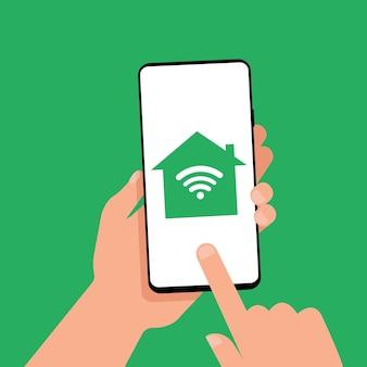 画面にスマートホームアイコンが表示されたスマートフォンを手で持っています。スマートフォンで家を管理しましょう。スマートテクノロジー