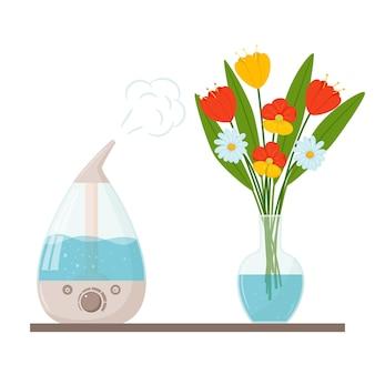 물이 담긴 투명한 유리 꽃병에 가습기와 꽃다발.