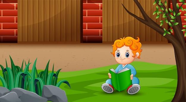 Маленький ребенок читает книгу на заднем дворе