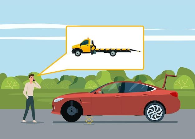 男が壊れた車の近くでレッカー車を呼びます。