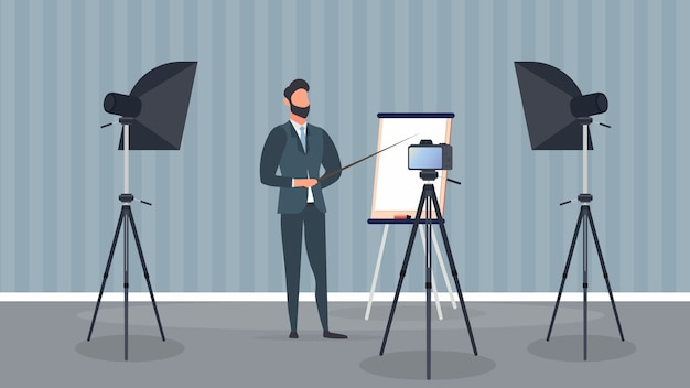 Мужчина в деловом костюме с галстуком проводит презентацию перед камерой. учитель пишет урок. концепция блогов, онлайн-тренингов и конференций. камера на штативе, софтбокс.