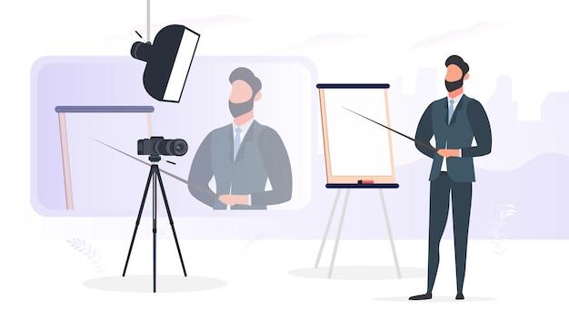 넥타이를 매고 비즈니스 정장을 입은 남자가 카메라에 프레젠테이션을 하고 있습니다. 선생님이 수업을 쓰고 있습니다. 블로깅, 온라인 교육 및 회의의 개념. 삼각대에 카메라, 소프트박스.