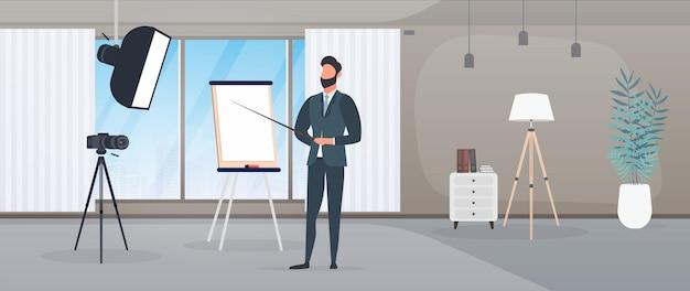 ネクタイをしたビジネススーツを着た男性がカメラにプレゼンテーションを行っています。先生はレッスンを書いています。ブログ、オンライントレーニング、会議の概念。三脚、ソフトボックスのカメラ。