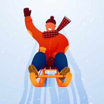 Мужчина катается на санях с горы по снегу.