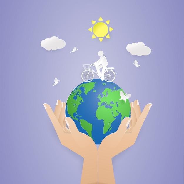 世界を持っている人間の2つの手で地球上で自転車に乗る男。