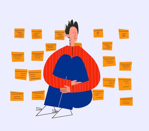 한 남자가 스티커 메모와 할 일 목록으로 둘러싸여 앉아 있다
