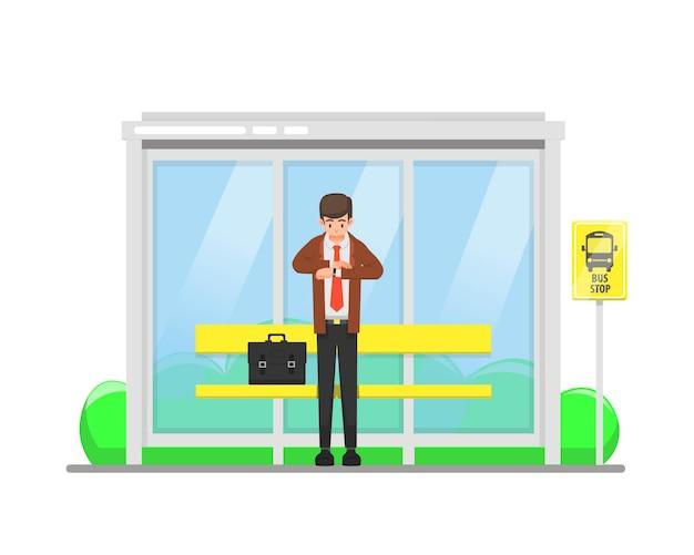 남자는 자신의 시계에서 시간을 보면서 버스 정류장에서 기다립니다