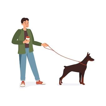 Мужчина с кружкой кофе в руке гуляет с собакой добермана