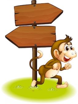 空の矢印板の横を走っている猿