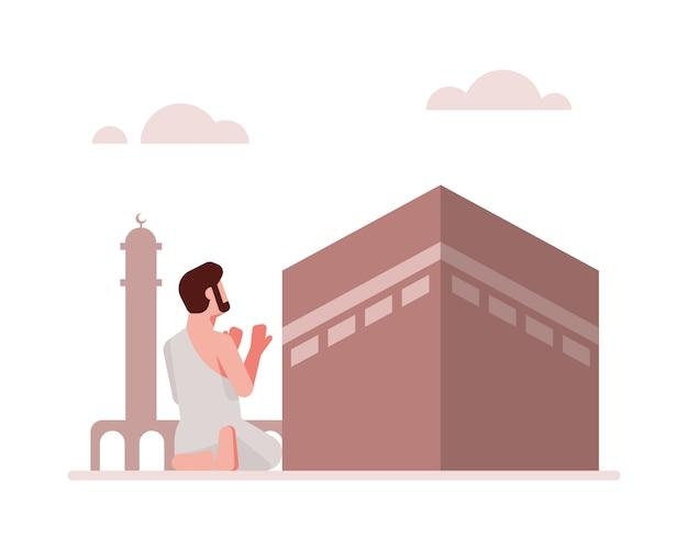 カーバ神殿イラスト背景の前で祈るイスラム教徒の男性