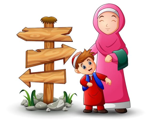 ムスリムの女性が彼女の息子の頭と空の木の矢印記号を保持