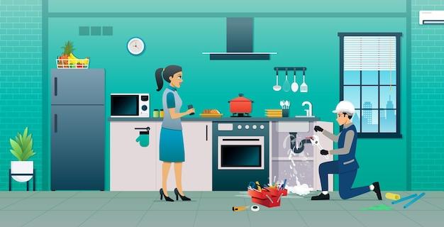 配管工が台所の漏れたパイプを修理しています。