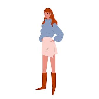 짧은 치마, 파란색 스웨터, 높은 갈색 부츠를 입은 예쁜 젊은 여성. 성인 소녀가 현대 캐주얼 옷을 입고 서 있습니다.