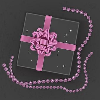 ピンクの弓で飾られたリアルな黒のギフトボックス、上面図。