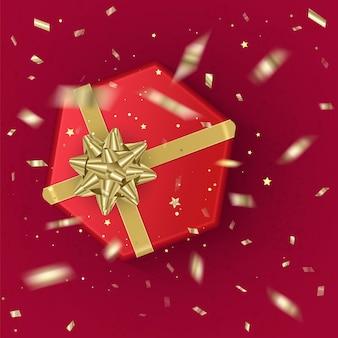 Реалистичная подарочная коробка красного цвета, украшенная золотым бантом, вид сверху.