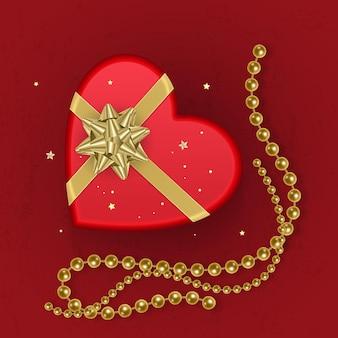 Реалистичная красная подарочная коробка в форме сердца, украшенная золотым бантом, вид сверху.