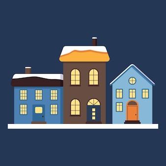 눈 속의 밝은 지붕, 창문과 굴뚝의 빛이 있는 작고 귀여운 집들. 새해와 크리스마스를 위한 메리 크리스마스 장식. 겨울과 축제 요소