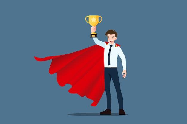 成功した青年実業家は赤いマントを着て、金のトロフィーカップを持ち上げて保持します。