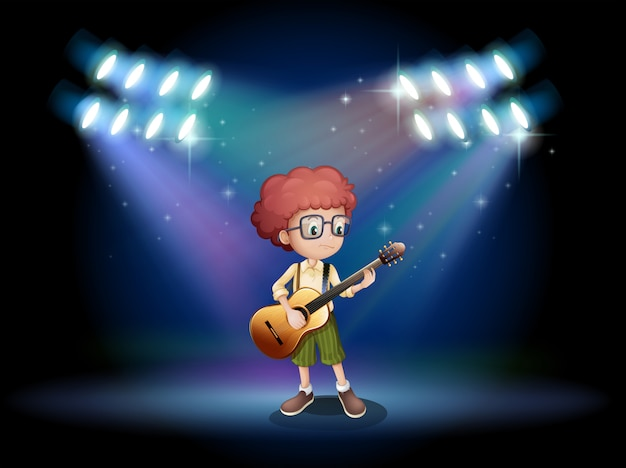 ステージの真ん中でギターを弾く才能のあるティーンエイジャー