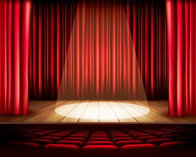 Театральная сцена с красным занавесом, сиденьями и прожектором.