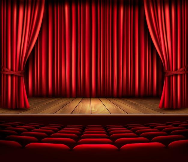 Сцена театра с красным занавесом, сиденьями и прожектором.