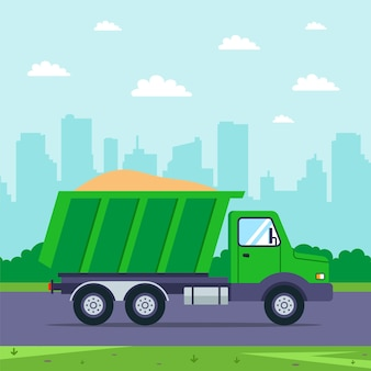 모래가 달린 트럭이 도시를 배경으로 도로를 주행합니다. 상품 운송.