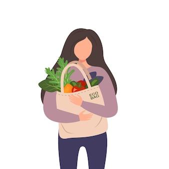 Женщина держит в руках текстильный мешок с овощами, делая покупки экологически чистых продуктов