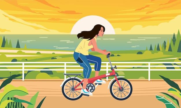 포스터 이미지 웹 사이트 이미지 및 기타에 사용되는 석양을 배경으로 해변 도로를 따라 자전거를 타는 여성