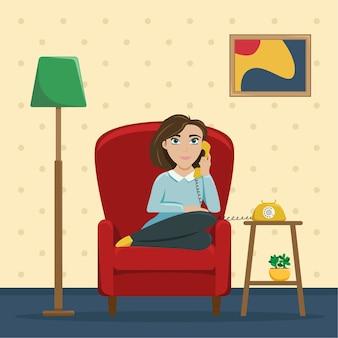 自宅の椅子に座って電話で話している女性。