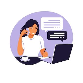 Женщина работает на портативном компьютере и разговаривает по телефону, сидя за столиком дома с чашкой кофе и бумагами.