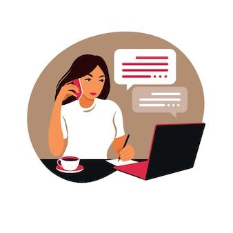 Женщина работает на портативном компьютере и разговаривает по телефону, сидя за столом дома