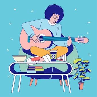 彼の前のソファと机に座って歌いながらギターを弾く若いアフロミュージシャン