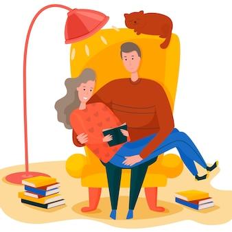 Молодая пара обнимается в кресле, читает книгу, уютная атмосфера.
