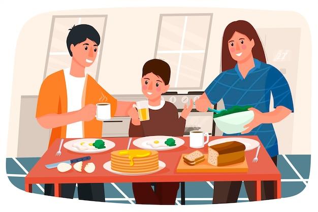若い家族が朝食をとっています。キッチン。料理。