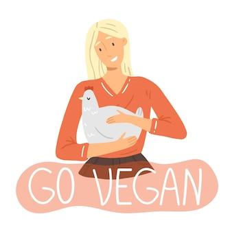 Молодая девушка держит в руках курицу, а надпись go vegan в розовом пузыре