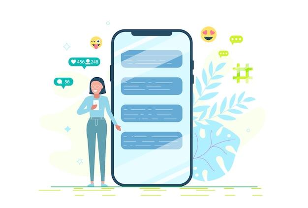 Молодая девушка стоит рядом с огромным смартфоном и пользуется собственными смартфонами с элементами социальных сетей и значками эмодзи.