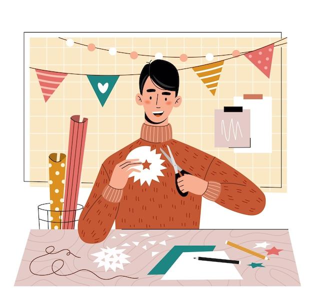 若い男が紙を切り取った。趣味。ホームレジャー。