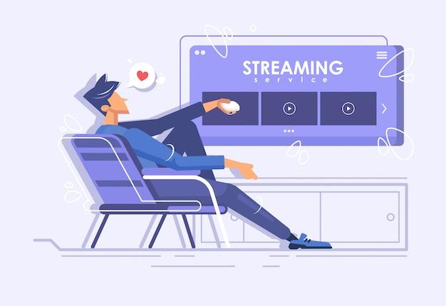 Молодой парень сидит в кресле и смотрит фильм. онлайн кинотеатр. концепция потокового обслуживания. онлайн просмотр сериалов на дому.