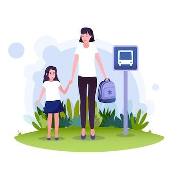 素敵な娘を持つ若い母親がバス停でスクールバスを待っています。