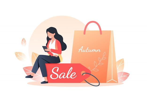 Молодая женщина держит в руках смартфон и сидит на скидочной бирке, подарках и покупках, осенних распродажах и интернет-покупках.