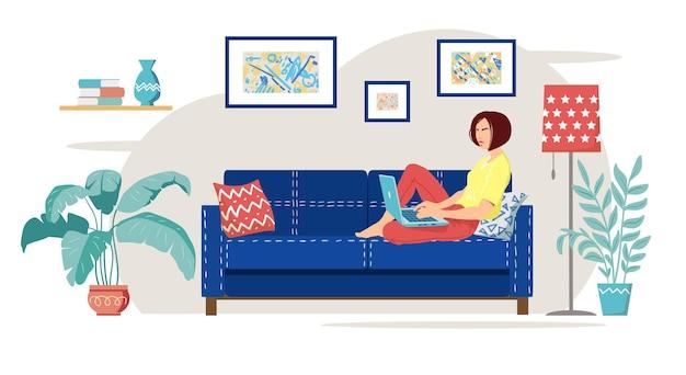 젊은 여성이 파란색 소파에 앉아 노트북으로 집에서 일하고 있습니다. 아늑한 현대적인 거실