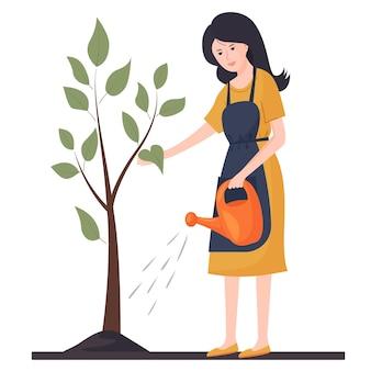 한 젊은 여성이 나무에 물을 주고 있습니다. 농업 일. 원예.