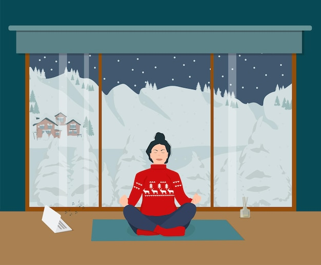 한 젊은 여성이 겨울 풍경을 바라보며 집에서 명상을 하고 있습니다. 요가와 휴식.