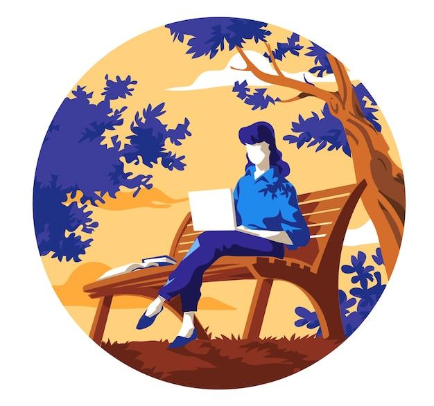 Молодая женщина, сидящая на скамейке в парке, работает на ноутбуке